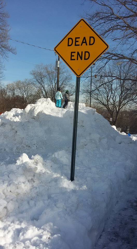 hill of snow with Dead End sign