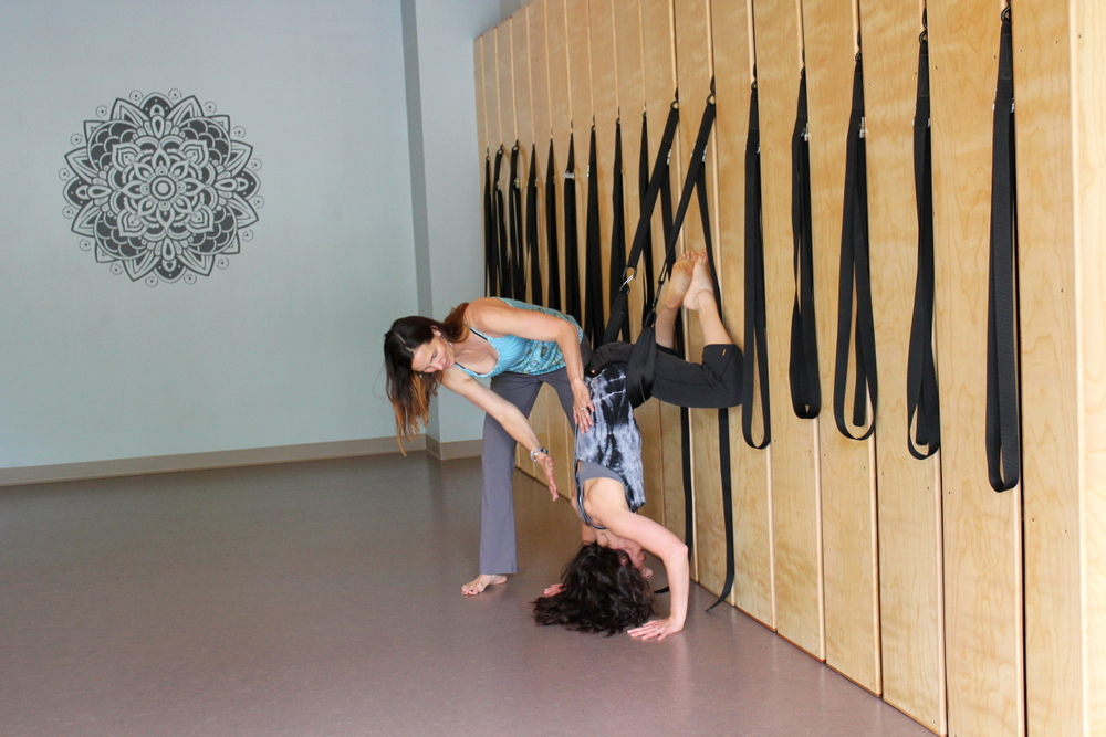 Ease Yoga Cafe by Mindful Healthy Life - Tara Casagrande assisting Rosie Wiedemer at yoga wall