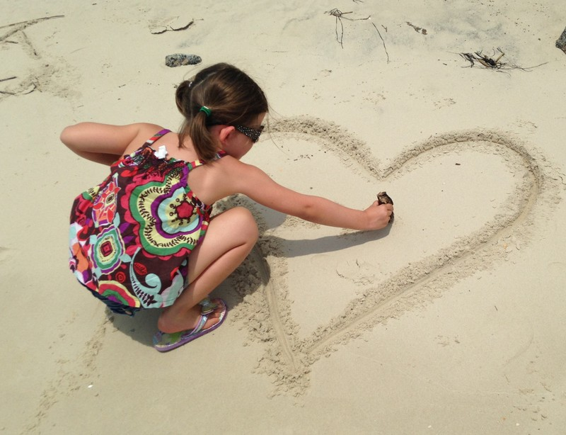 Drawing heart in the sand